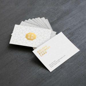 Imagem de uma pilha de cartões de visita sobre uma mesa de cor escura.
